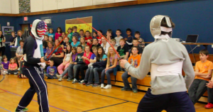 Tim Morehouse and Jeff Spear duel in front of students in Maine during their Fencing In The Schools assembly. Courtesy of Holly Buechel